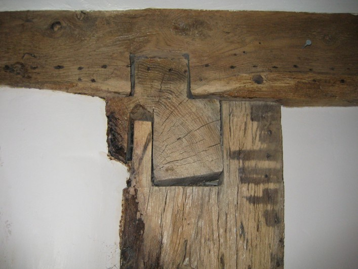 The original cross wing corner post showing section through the bressumer beam which has been cut away, and the overhanging cantilevered floor joists which are gently chamfered.