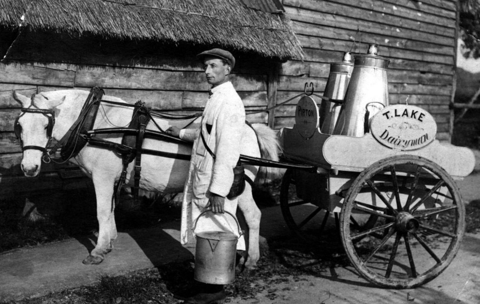 """1926 Tom Lake, Pirton's first milkman, with his churns, pails and measuring jugs. He delivered milk twice a day as there were no fridges to keep milk cool. Milk was """"straight from the cow"""" and was not pasteurised as is now required by health legislation"""