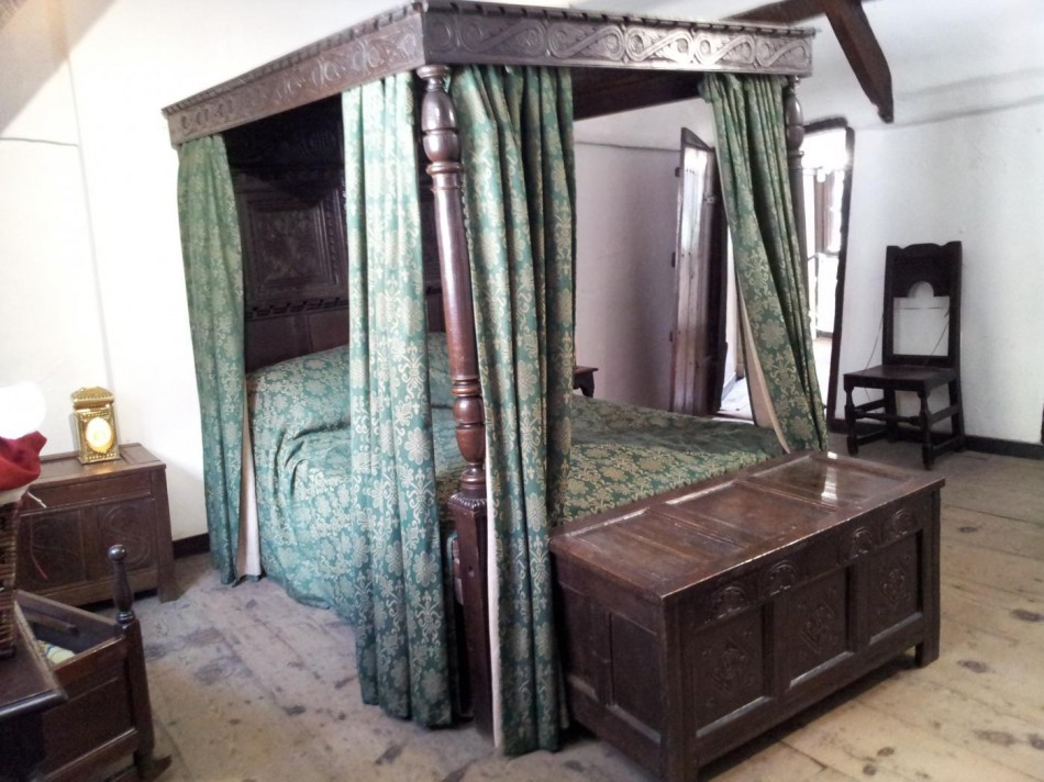 A posted bed with 4 posts with a wooden canopy or ceiling.The coffer at the foot of the bed was for the linen.