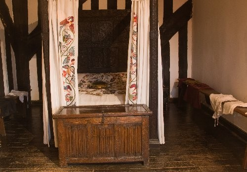 A grander bed with  hand embroidered crewel work curtains.the beds often had 2  mattresses ,made of feather, flock or in poorer cases straw.