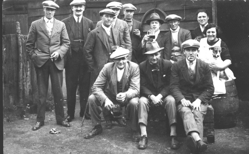 1938  A group of regulars outside the Red Lion with the landlord Matt Mackenzie. Back row L-R: Cecil Day, Matt Mackenzie, Bob Males, Charlie Males, George Males, Len Dawson, Phil Reynolds, Mrs Newberry, cleaner. Front row L-R: Cecil Stapleton, Len Baines, Fred Furr.