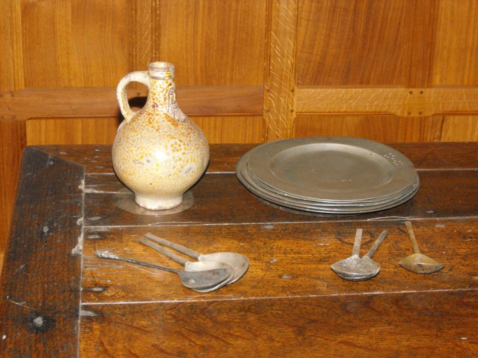 Pewter plates and spoons. The stoneware bellarmine flagon has a bearded face of a man on it.