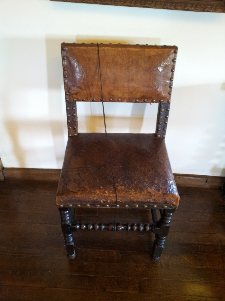 A chair upholstered in leather.Chairs were upholstered from at least the 16th Century.