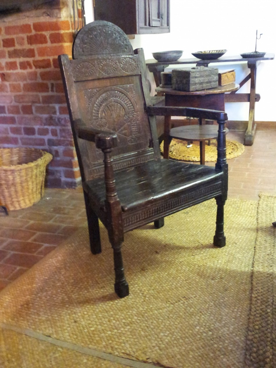 An carved oak chair with arms.